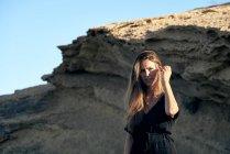 Joven de pelo largo elegante mujer pensativa de pie en la luz del sol con roca en el fondo - foto de stock