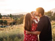 Cheerful couple kissing little dog among high grass in countryside — Stock Photo