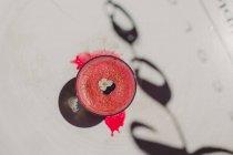 Smoothie rose parfumé mousseux mousseux décoré de fleurs en verre sur une surface blanche avec ombre — Photo de stock