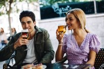 Alegre joven atractiva pareja disfrutando de bebidas refrescantes durante la fecha de la ciudad - foto de stock