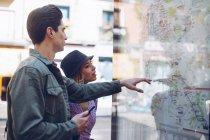 Joven pareja atractiva de turistas mirando el mapa en la calle - foto de stock