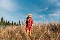 Улыбающаяся женщина в соломенной шляпе и красном платье, стоящие на диком поле на фоне голубого неба — стоковое фото