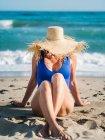 Тонкая загорелая женщина в синем купальнике и шляпе, прячущая лицо и сидящая со скрещенными ногами на песчаном пляже в яркий день — стоковое фото