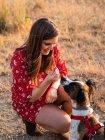 Молодая женщина с длинными волосами, играющая и любящая симпатичную собаку — стоковое фото