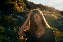 Ritratto di giovane donna in piedi nella natura nella soleggiata giornata estiva — Foto stock