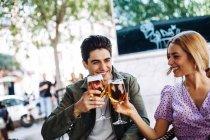 Joyeux jeune couple attrayant profitant de boissons rafraîchissantes dans le café de la ville — Photo de stock