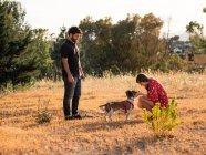 Couple gai jouer avec petit chien amical dans la nature — Photo de stock