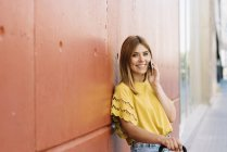 Молодая женщина разговаривает по мобильному телефону опираясь на красную стену — стоковое фото