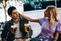 Веселая молодая привлекательная пара, наслаждающаяся освежающими напитками в кафе — стоковое фото