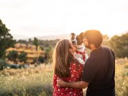 Couple kissing little dog in sunny countryside — Stock Photo