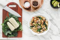 Served bowl with mushrooms, corn and cut chicken salad on table with corn leaves of greenery on cutting board and condiments — Stock Photo