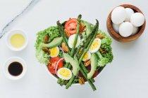 Подається чаша салату з спаржею, яйця, авокадо, помідори, волоські горіхи і зелень на столі з приправами, соусами і яйцями — стокове фото