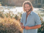Young cheerful bearded hipster man unbuttoning blue shirt preparing to swimming in river — Stock Photo