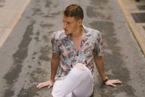Handsome male in Hawaiian shirt sitting on asphalt on street with crossed legs and looking away — Stock Photo