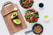 Bowls with strawberries, almonds and greenery on table with avocado and spoon of sauce on cutting board — Stock Photo