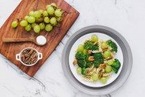Cuenco servido de ensalada con macarrones, brócoli y pacanas sobre la mesa con uvas y sal sobre tabla de cortar - foto de stock