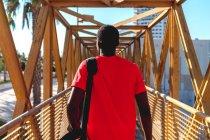 Невпізнанний Атлетичний чоловік у спортивному одязі з мішком ходьба на жовтий Залізний міст в Сонячний денний — стокове фото