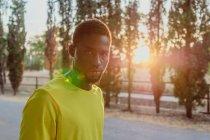 Determinado deportista hombre afroamericano mirando sin emoción a la cámara de pie en brillante retroiluminación - foto de stock