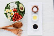 Cuenco servido de ensalada con espinacas, huevos, aguacate, tomates y queso mozzarella sobre la mesa con condimentos y salsas - foto de stock