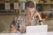 Focalisé jeune homme parlant sur smartphone tout en utilisant un ordinateur portable à la table à travers les fenêtres dans un café — Photo de stock