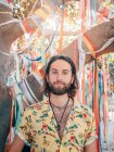 Pensieroso bello barbuto hipster uomo in piedi sotto albero decorato guardando in macchina fotografica — Foto stock