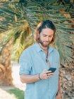 Молодой бородатый хипстер в синей рубашке пишет смс на мобильный телефон в тропических джунглях — стоковое фото