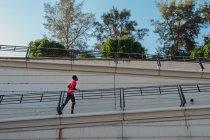 Vista laterale del corridore afroamericano attivo che corre su un ponte inclinato in pieno sole diurno — Foto stock