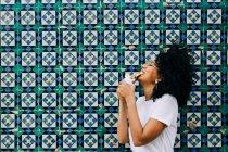 Jeune femme en t-shirt blanc debout près du mur de tuiles colorées, gaufre mordante — Photo de stock