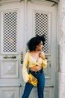 Trendy donna afroamericana in crop top giallo e jeans in piedi dalla porta e guardando altrove — Foto stock