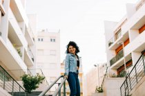 Fashionable African American woman in crop top and jeans leaning on railing and smiling — Stock Photo
