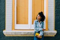 Модні етнічні жінки в джинсах і джинсового куртка тримає моду сумочку і спираючись на яскравий підвіконня на відкритому повітрі — стокове фото