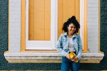 Mujer étnica de moda en jeans y chaqueta de mezclilla sosteniendo bolso de moda y apoyándose en el alféizar de la ventana brillante al aire libre - foto de stock