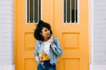 Joven mujer afroamericana en jeans y chaqueta de mezclilla apoyada en la puerta amarilla, sujetando el embrague y mirando hacia otro lado - foto de stock