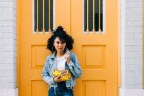 Joven mujer afroamericana en jeans y chaqueta de mezclilla apoyada en la puerta amarilla, sujetando el embrague y mirando a la cámara - foto de stock