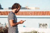 Giovane maschio che cammina con il cellulare — Foto stock