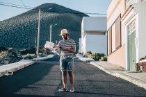 Viaggiatore maschile in piedi con mappa e smartphone sulla strada — Foto stock
