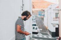 Giovane maschio in piedi in città con il telefono cellulare — Foto stock