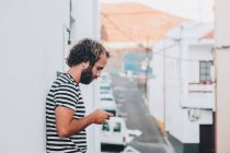 Giovane maschio in piedi su strada con cellulare — Foto stock
