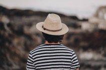 Homme élégant en chapeau sur route déserte, vue arrière — Photo de stock