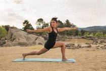 Femme adulte moyenne s'étirant tout en faisant du yoga à l'extérieur sur la plage du barrage — Photo de stock