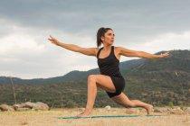 Взрослая женщина растягивается во время занятий йогой на открытом воздухе на дамбе пляжа — стоковое фото