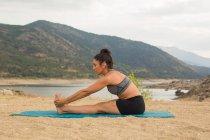 Взрослая женщина, сгибающаяся во время занятий йогой на дамском пляже — стоковое фото