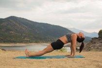 Mulher adulta meados de que faz a ioga ao ar livre na praia da represa — Fotografia de Stock
