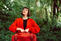 Frau in Rot mit großem roten Koffer im Wald — Stockfoto