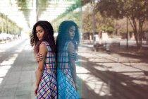 Вид сбоку на молодую этническую женщину, обнимающую себя, стоящую у стеклянной стены с отражением на улице — стоковое фото