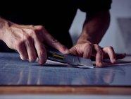 Руки профессионального человека, режущего листы бумаги специальным острым ножом на рабочем столе — стоковое фото