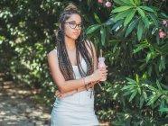 Модная молодая женщина в очках с дредами пьет коктейль и смотрит в камеру в саду — стоковое фото