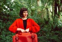 Frau in Rot mit großem Vintage-Koffer steht im Wald und lächelt — Stockfoto