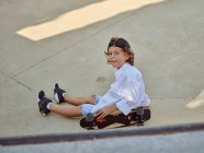 Felice bambino seduto e agghiacciante a terra con skateboard in skatepark guardando in macchina fotografica — Foto stock