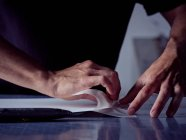 Hands of skillful agile craftsman gluing pages together on working table — Stock Photo